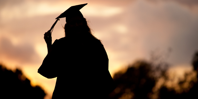 A graduate in cap and gown is silhouetted by sunset.